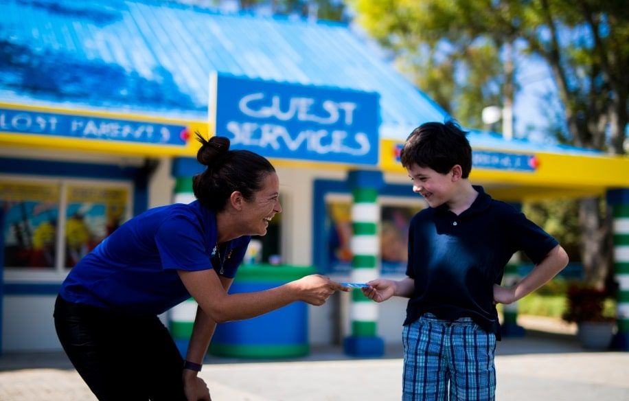 Guest Services at Lego Land giving a child with autism a ticket and smiling