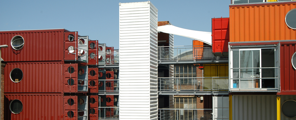 stack of red shipping container apartments with a white elevator shaft at Container city I in London