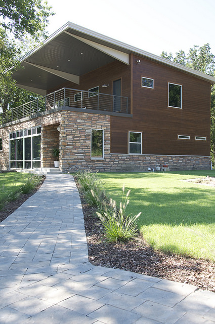 Brown two story house with stone walls wrapping a shipping container construction