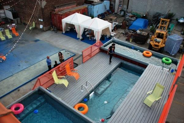shipping container pool surrounded by deck chairs and cabanas