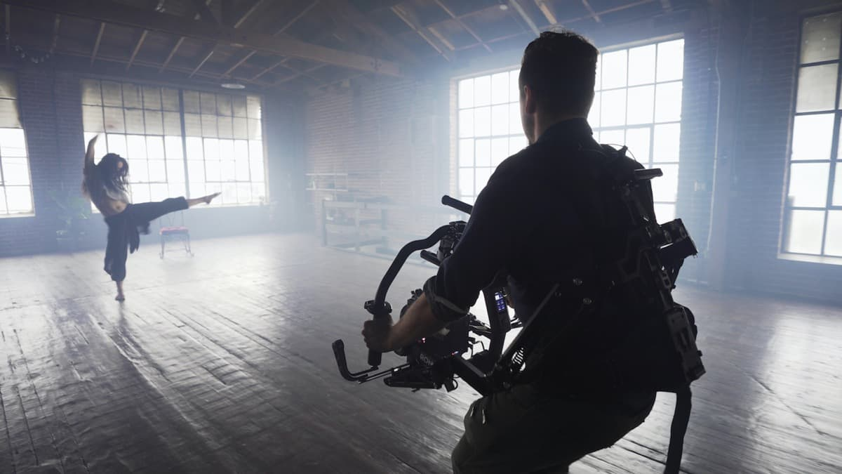 A cameraman films a dancer in an empty studio.