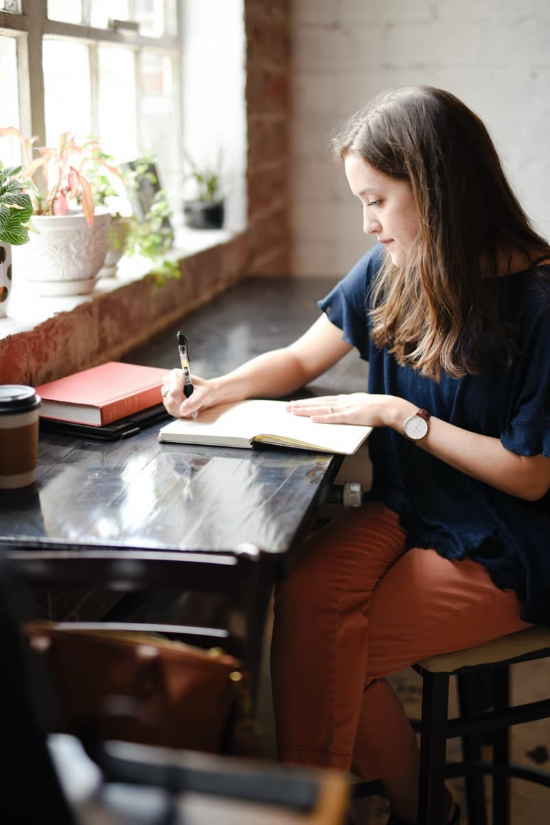 A writer sits at her desk writing in a journal.
