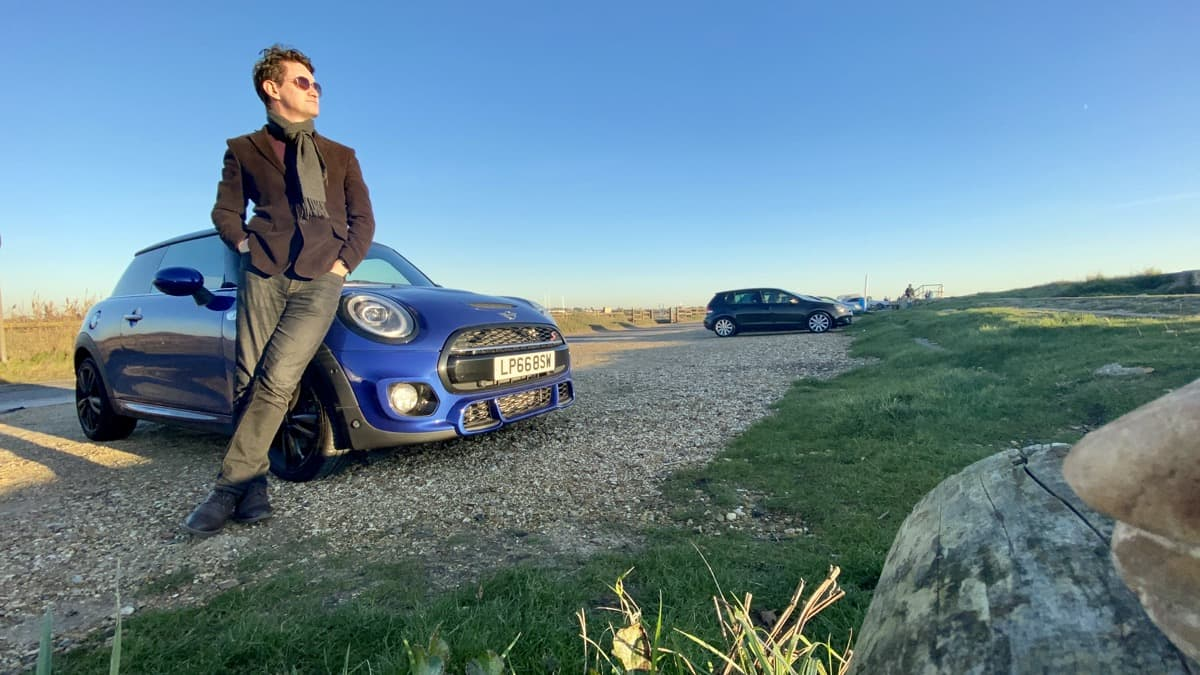 James standing next to his car in the countryside.