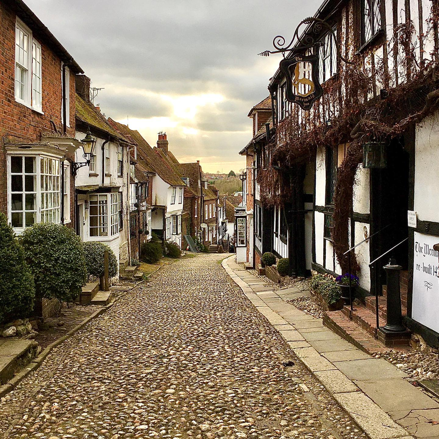 Glancing across the cobblestones of the famous Mermaid Street in Rye, Sussex.   The Mermaid Inn, established in 1156 and rebuilt in 1420, is one of the most significant structures in this quaint Medieval fishing village.  #rye #sussex #england #history #architecture #medieval #pub #iconic #village #villagepub #photography #outdoors #beautiful #cobblestone #story #sun #sunshine #tourism #uk