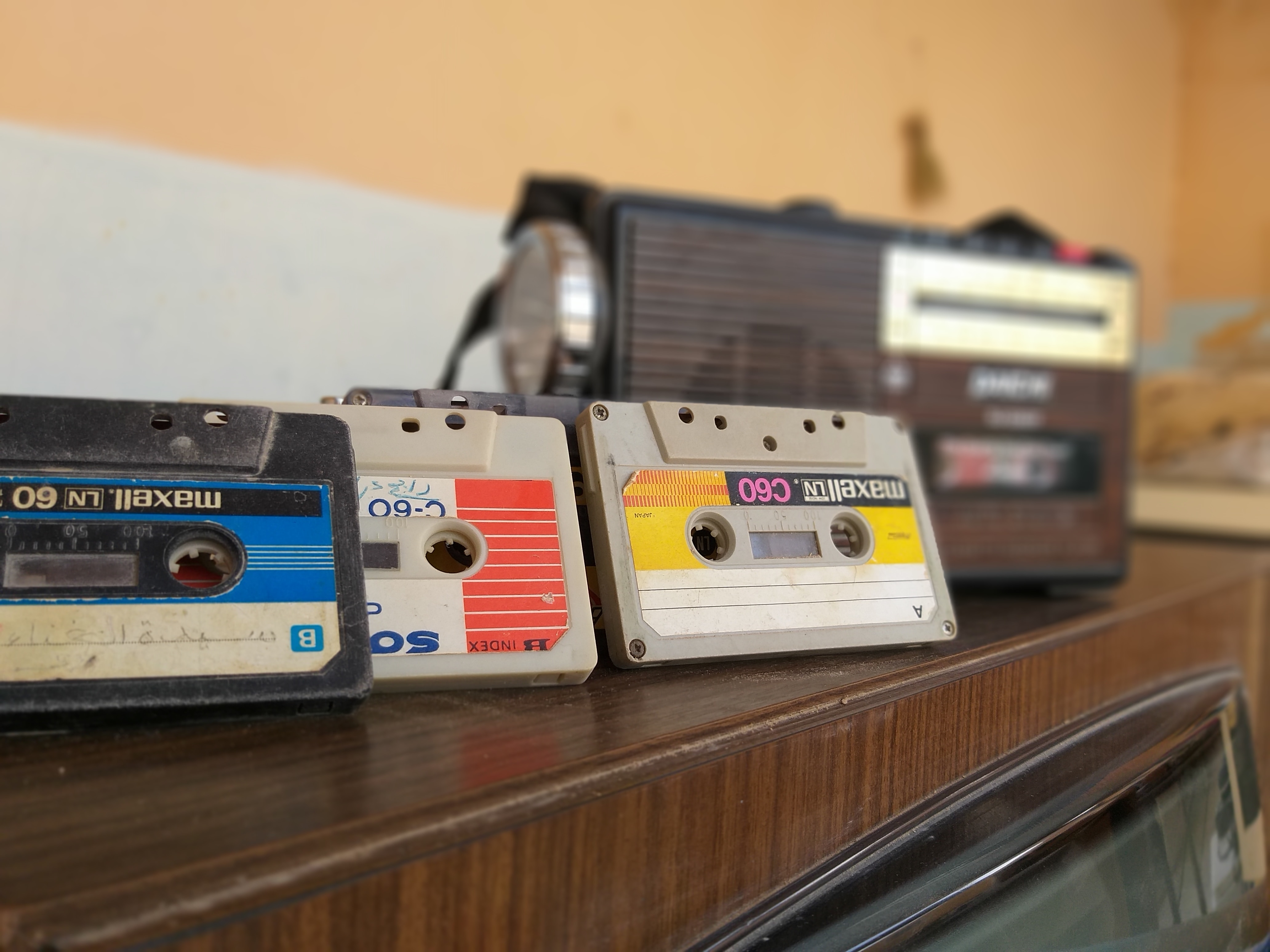 cassette tapes on a wooden tv stand
