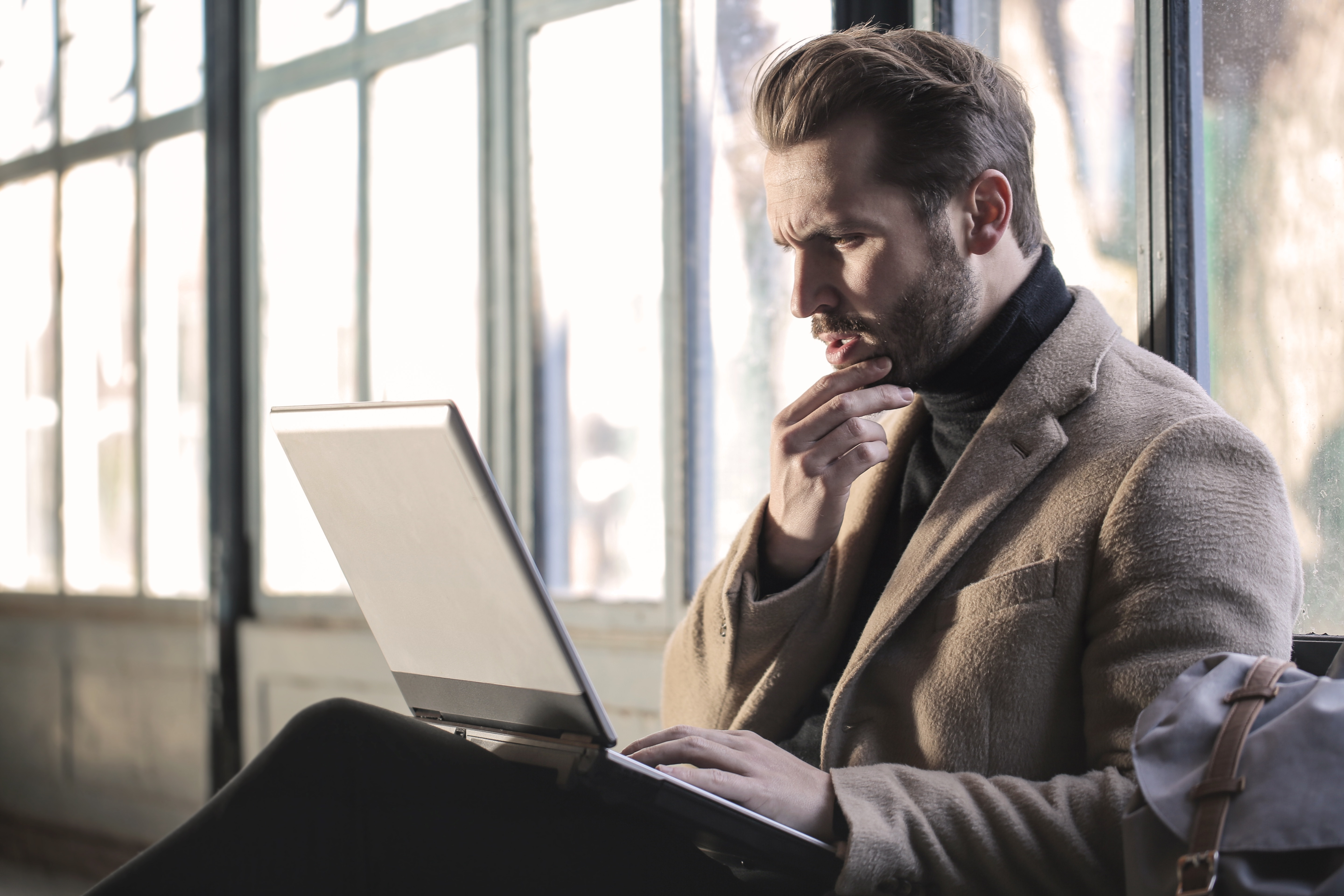 man thinking while sitting holding a laptop