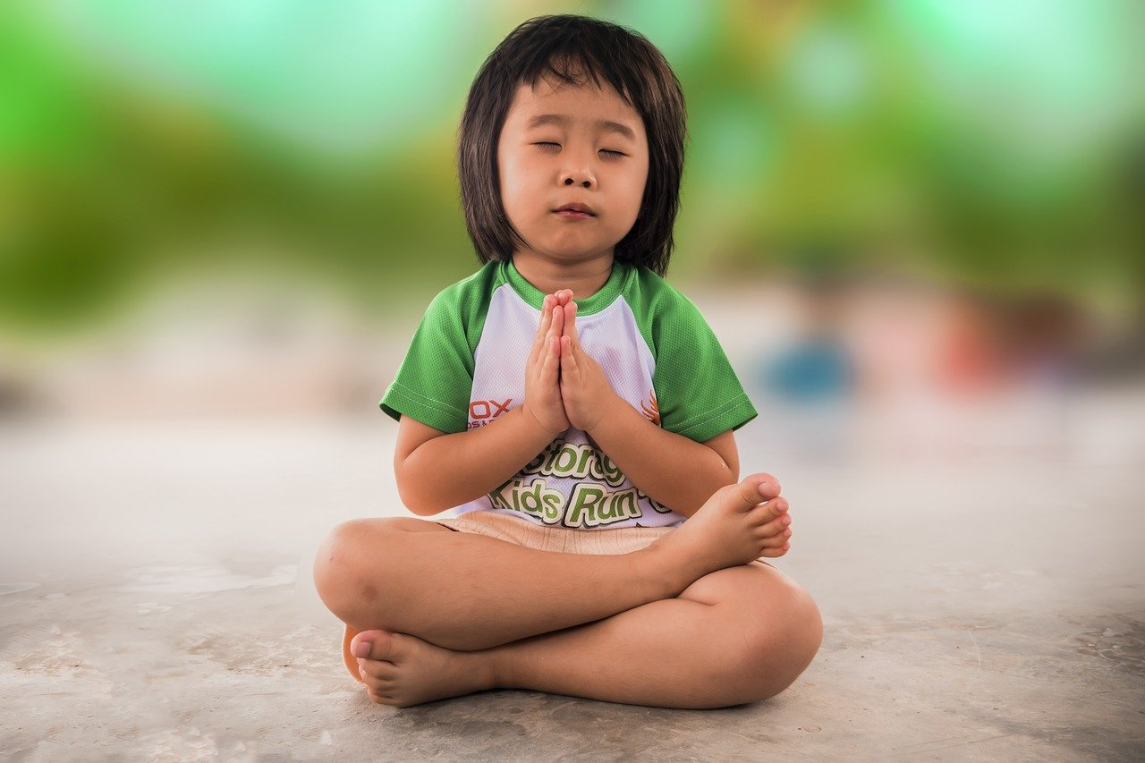 girl in green and white shirt praying