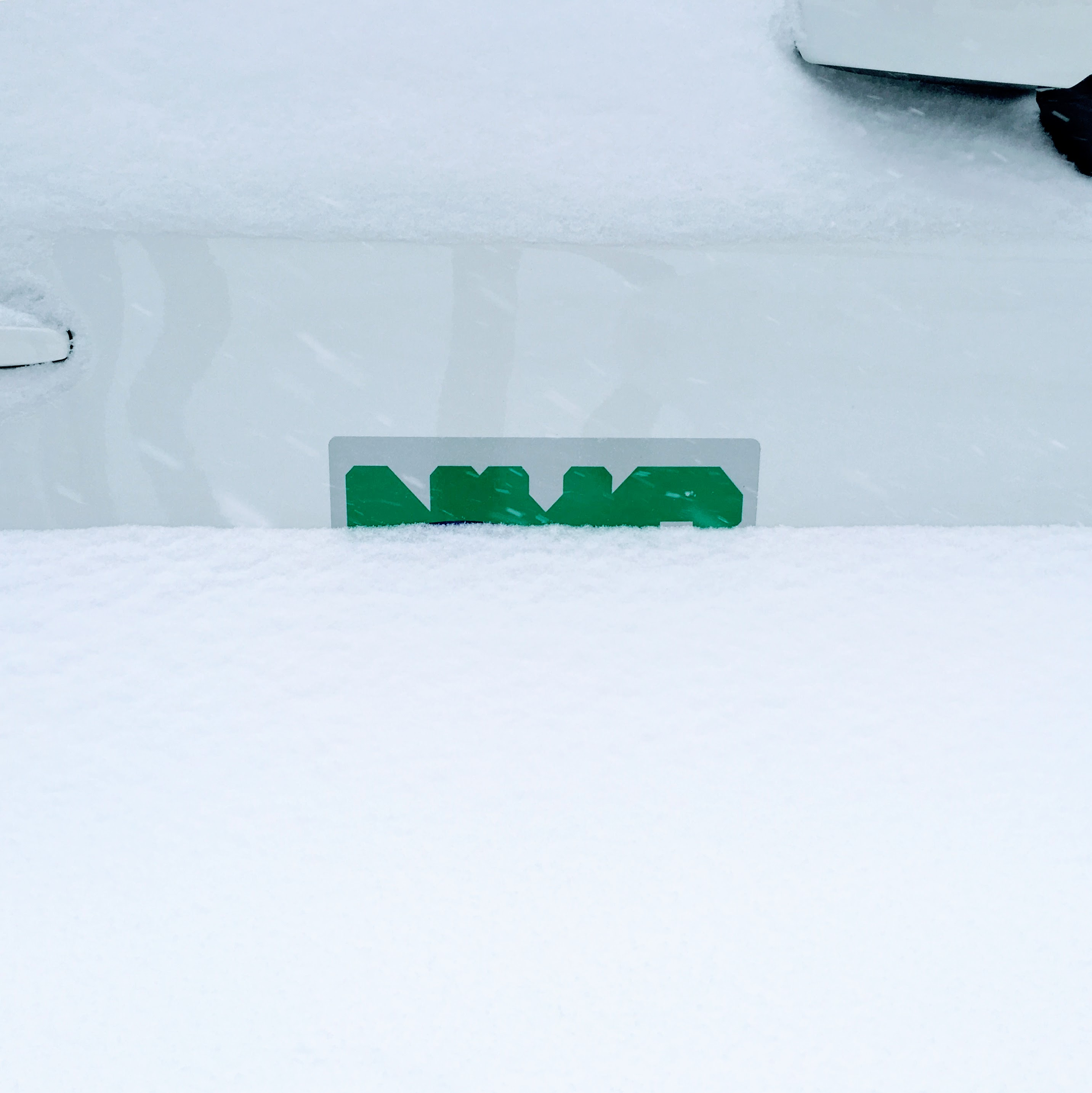 snow covering nyc city worker car logo in green