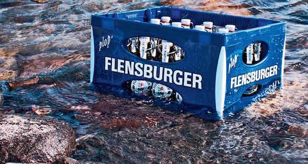 Ein Kasten Felnsburger Bier, der in flachem Wasser auf Steinen steht.