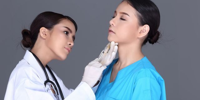 woman doctor giving woman patient an injection under chin