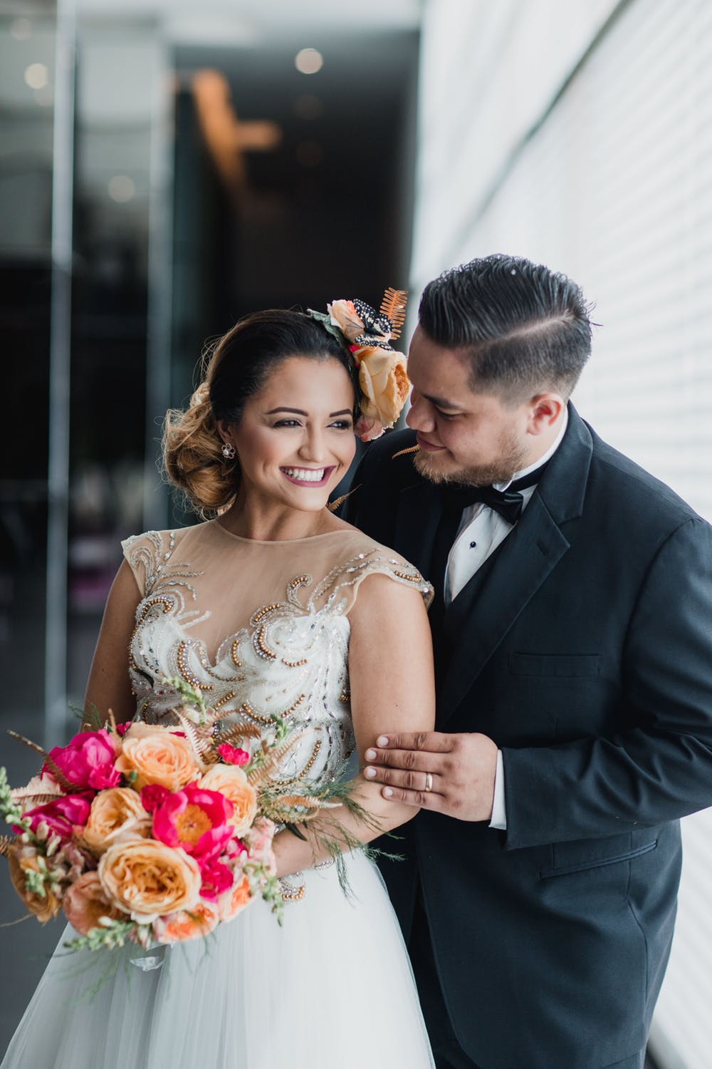 white bride and groom holding flowers