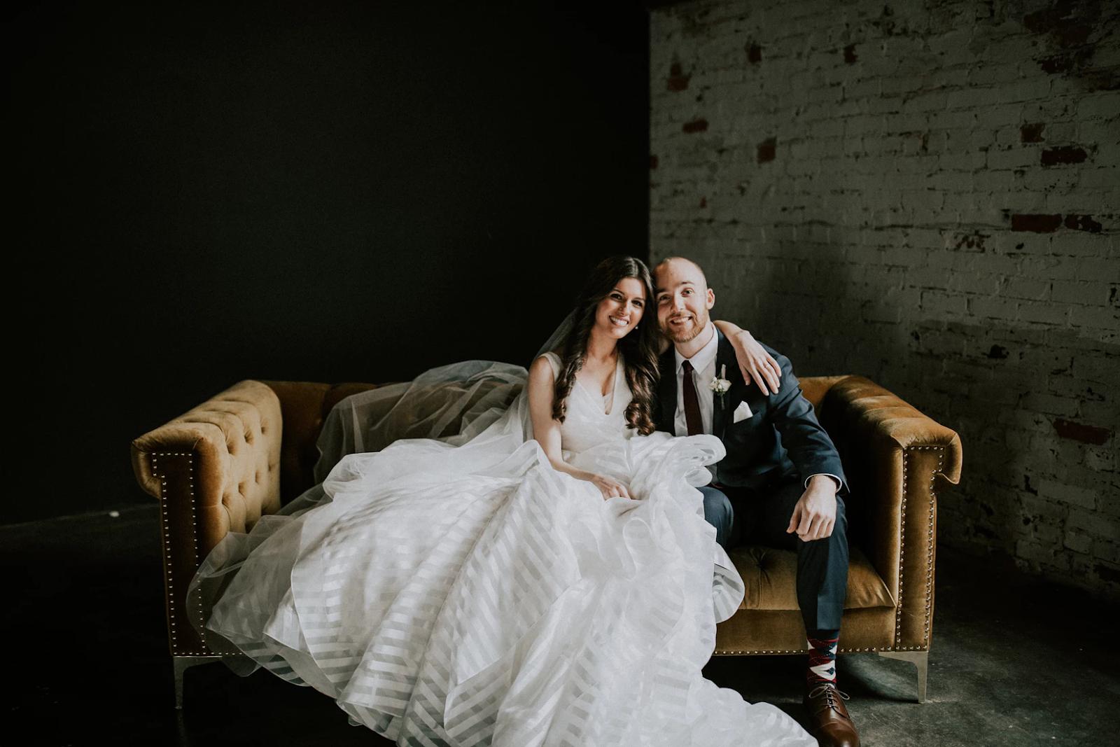 white bridge and groom sitting on brown sofa
