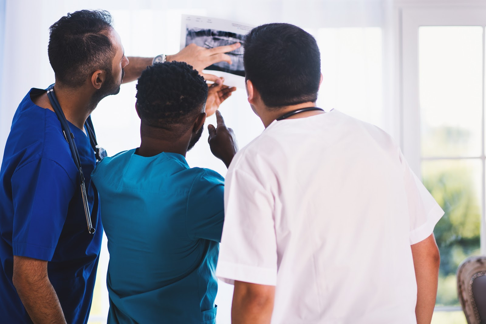 three male dentists looking at an x-ray