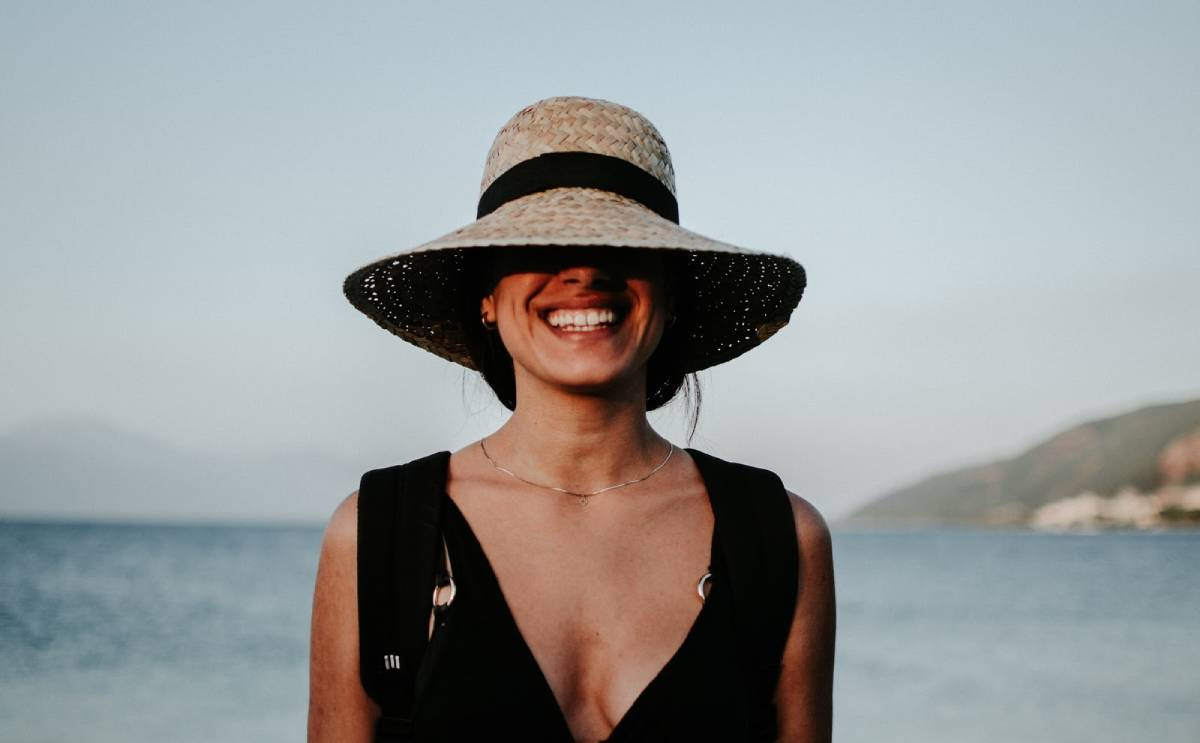 smiling woman in hat standing in front of beach