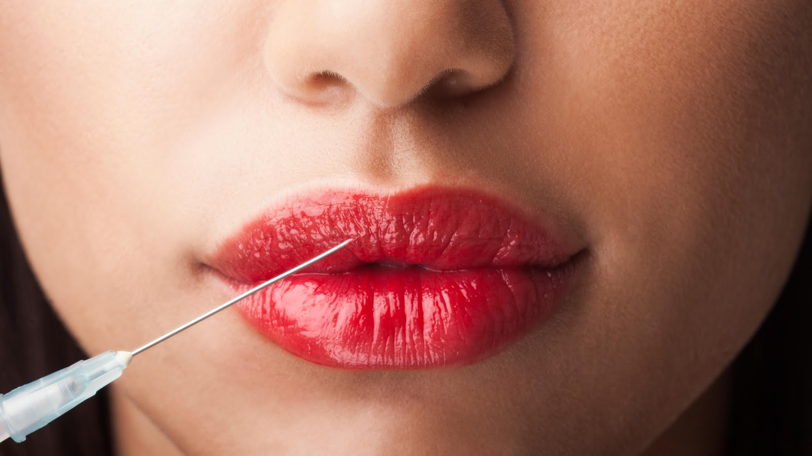 a woman sticking needle into her lips