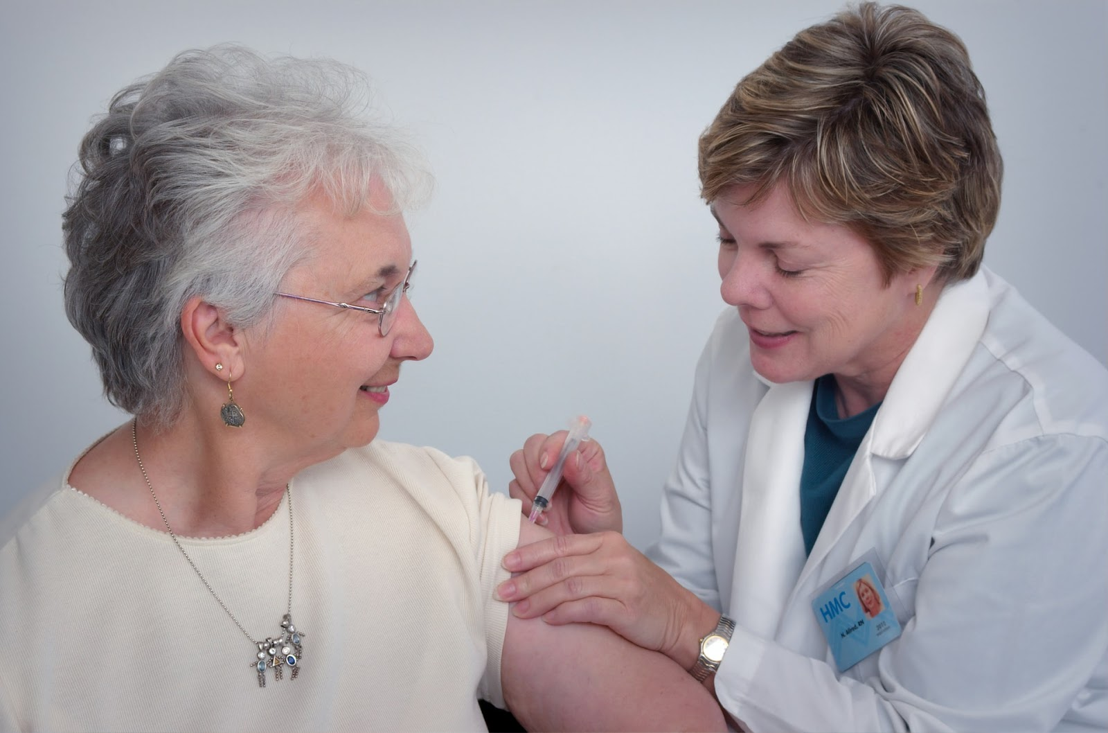 female physician giving patient a shot