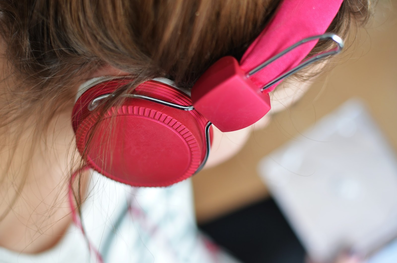 female wearing set of red headphones