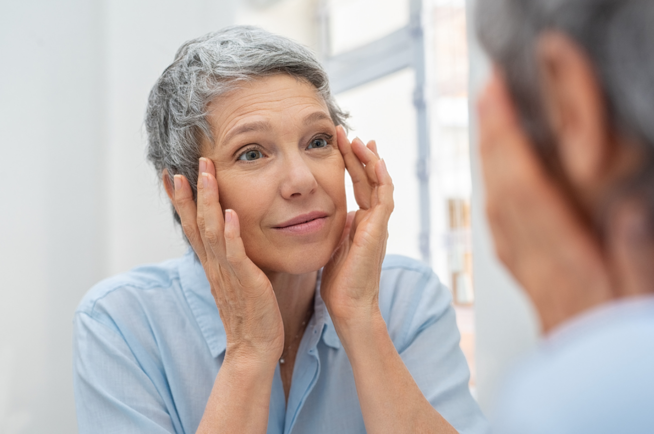 Older woman looking at her face in the mirror