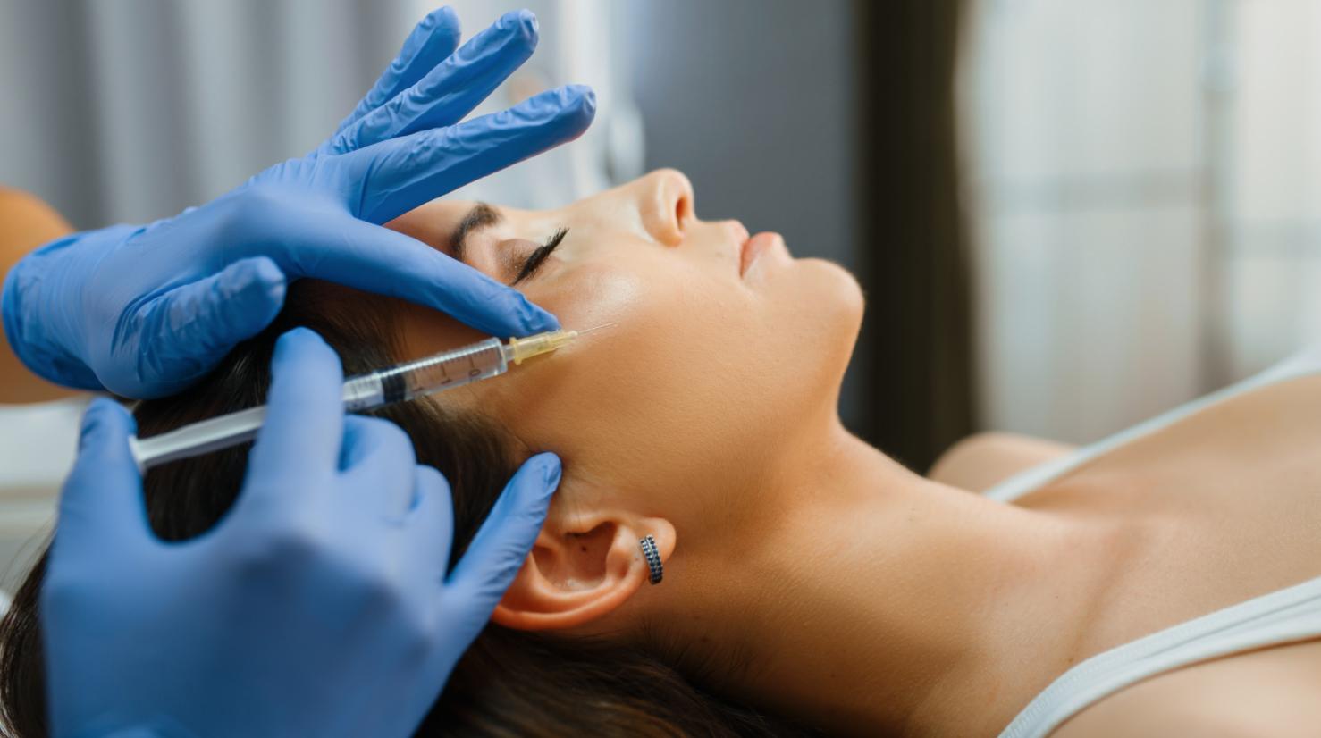 woman lying down getting cheek injected