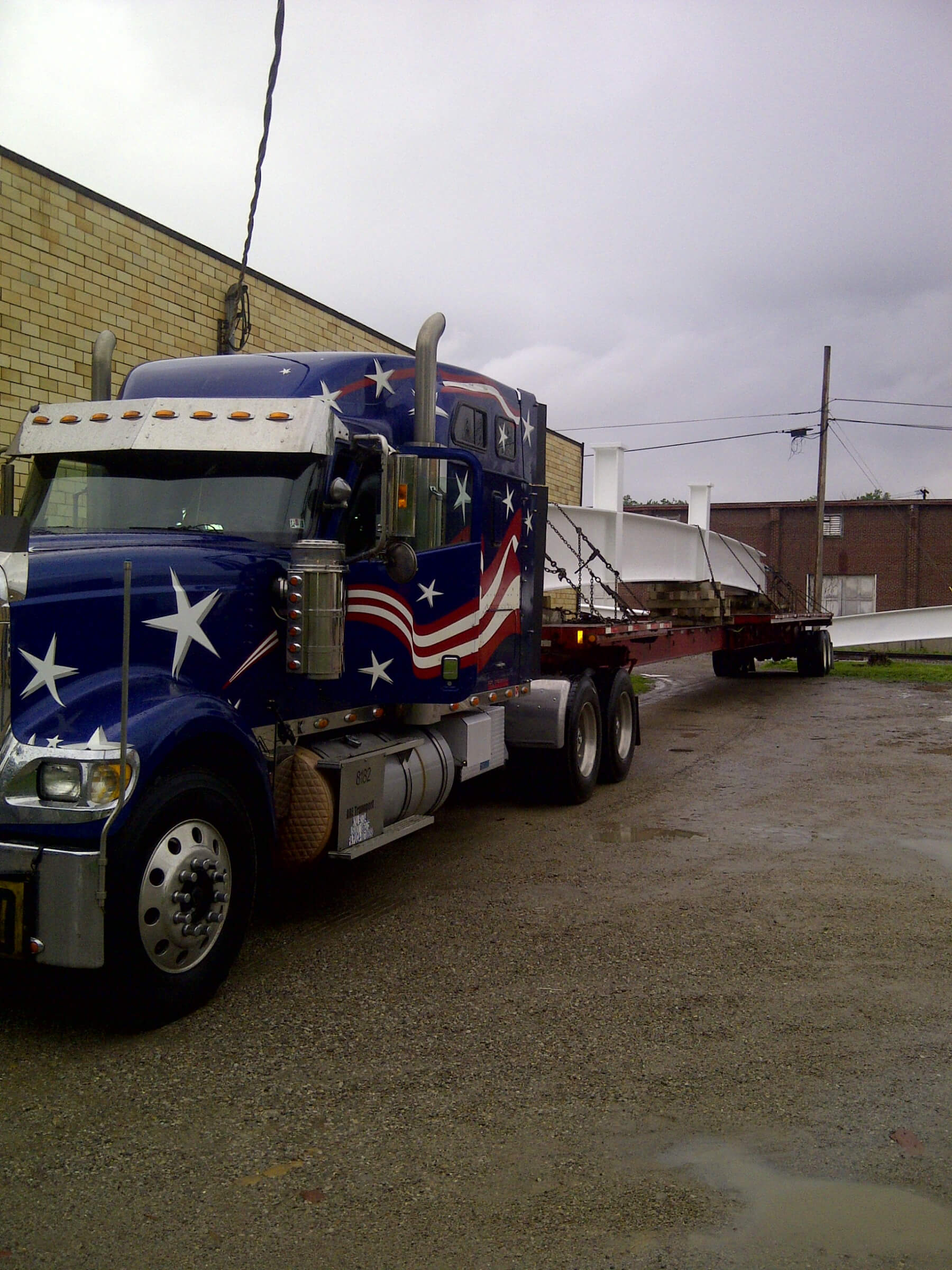 American Flatbed Truck hauling construction piece