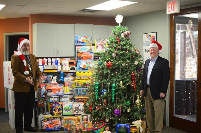 Shawn Slavin and Gary Crouch standing next to a large stack of toys and a christmas tree