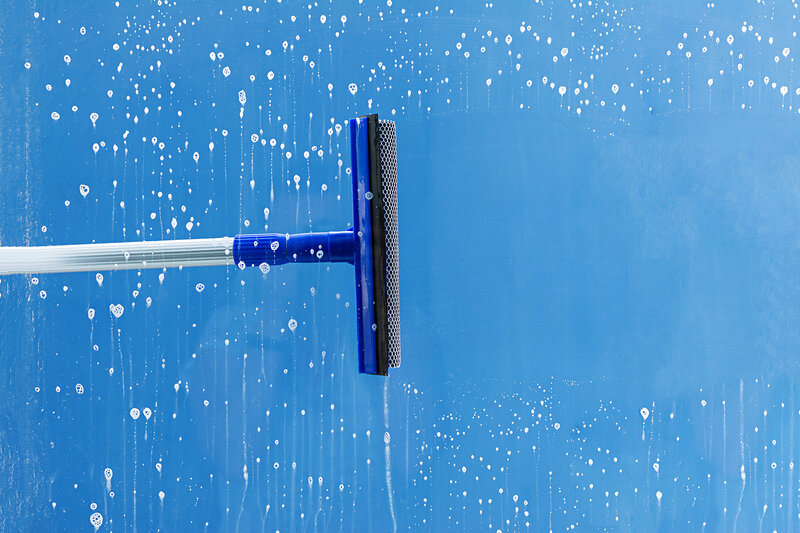 cleaning the window using a rubber squeegee