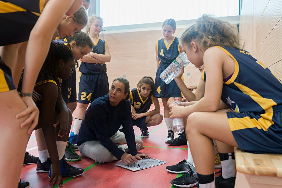Female basketball coach teaching a group of young players