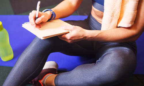 A woman in workout clothes writing down her fitness goals to make exercise intentional