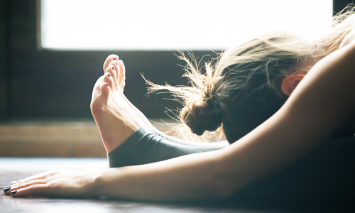 A woman stretching as part of her pre-workout ritual