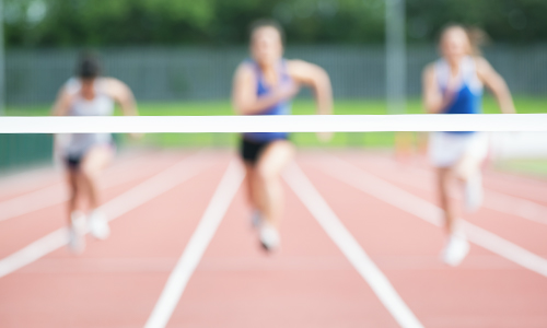 Three women sprinting toward a finish line to illustrate that fitness goals should be realistic and achievable
