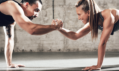 A woman shaking hands with her male personal trainer in between push ups
