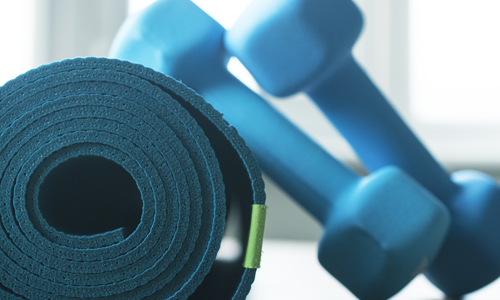 A blue yoga mat and two dumbbells are some basic home gym equipment essentials