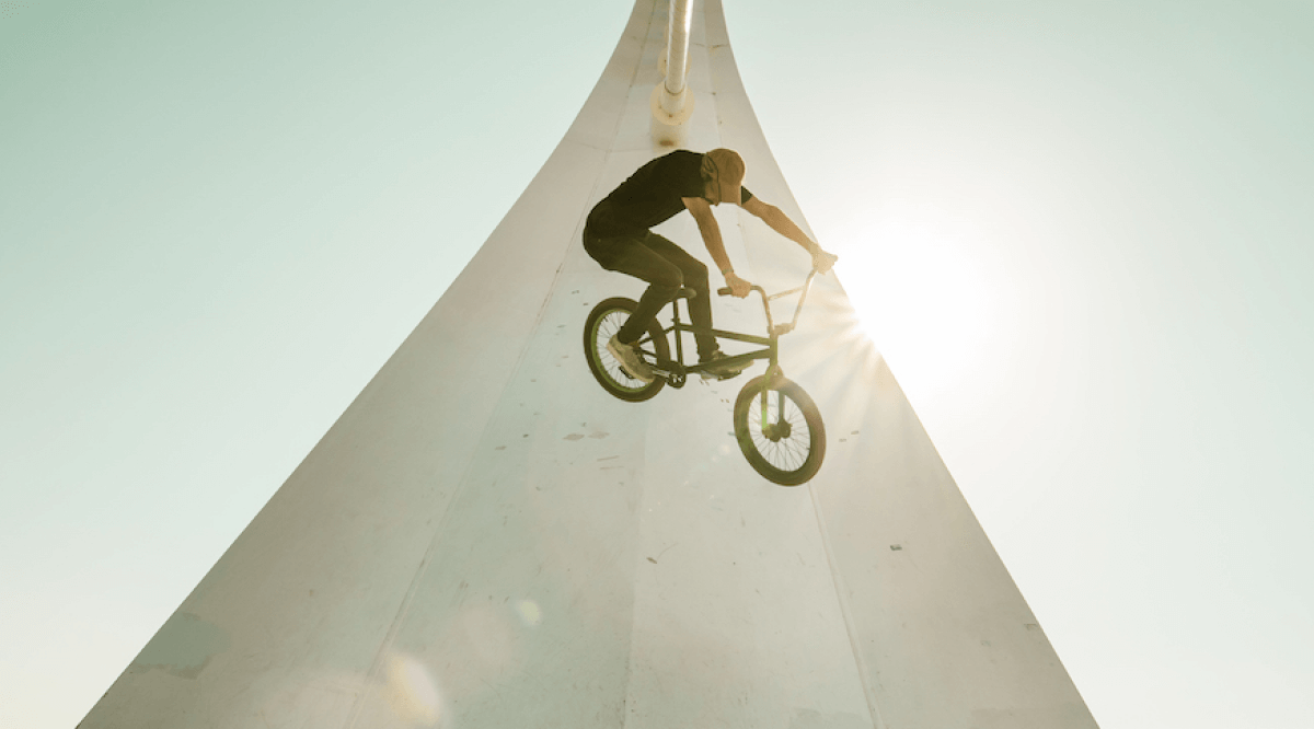 BMX rider doing tricks with the sun in the background