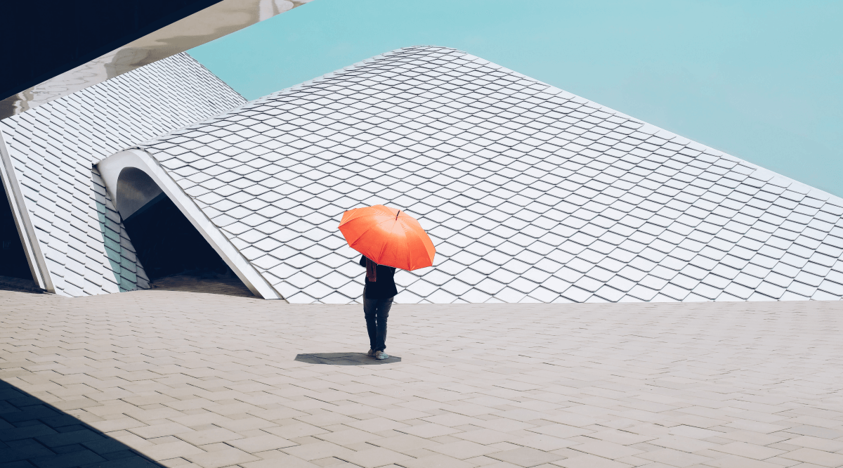 Low section of person with umbrella walking by modern building