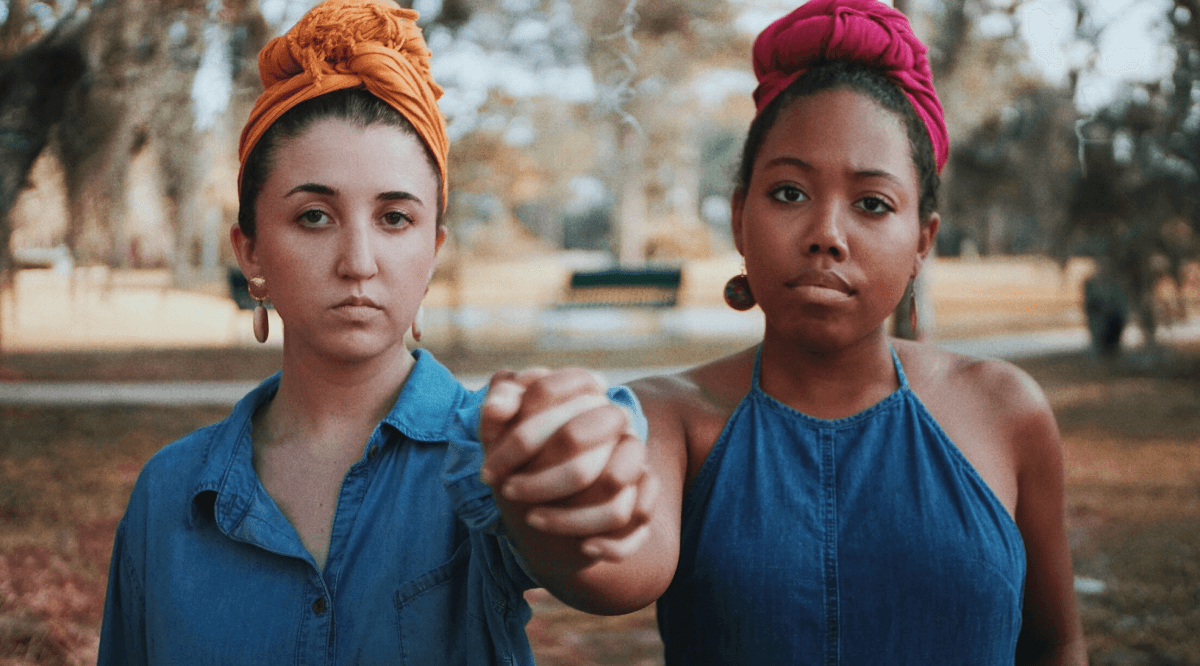 Portrait of young women holding hands while standing at park