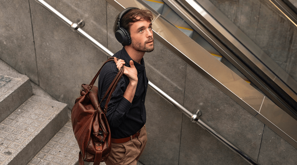 Man wearing Sennheiser headphones as he walks down a set of stairs
