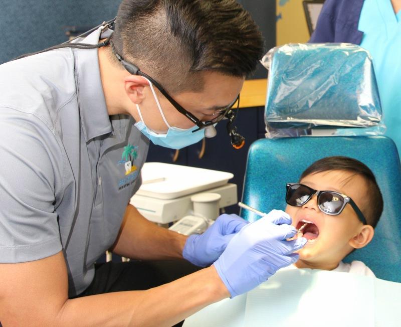 Pediatric dentist examining patient
