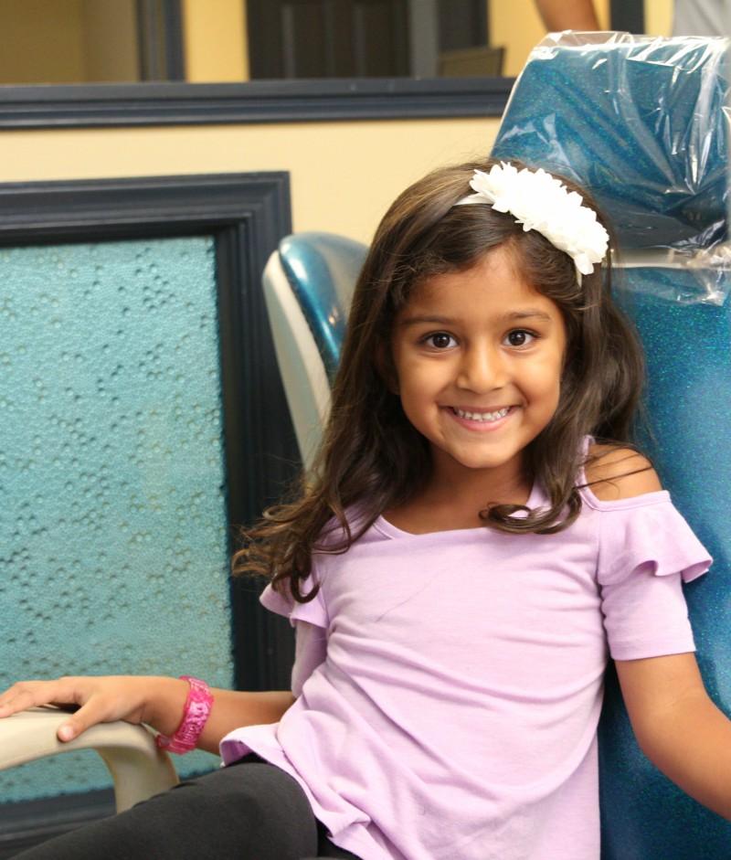 little girl smiling in dental chair