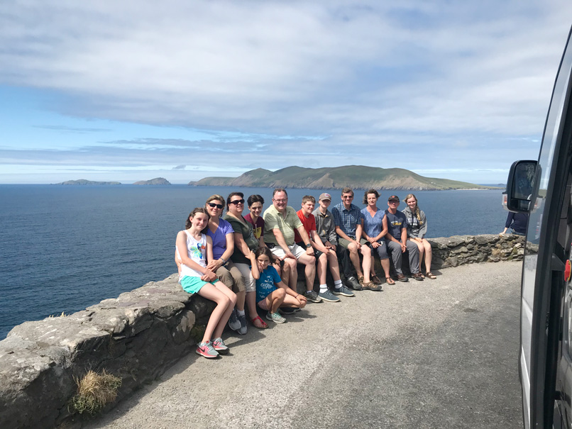 A happy tour group on the Slea Head Drive with the Great Blasket Island across the bay on the Dingle Peninsula