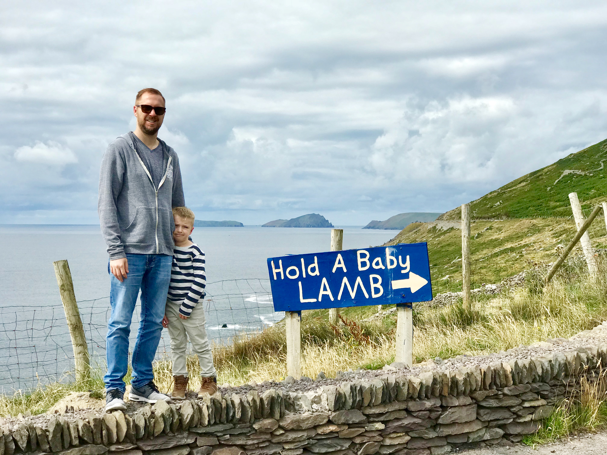 A man and boy standing in front of a panoramic view of the Blasket Islands on Dingle Peninsula's Slea Head Drive