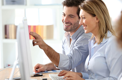 Man and woman looking at computer screen smiling