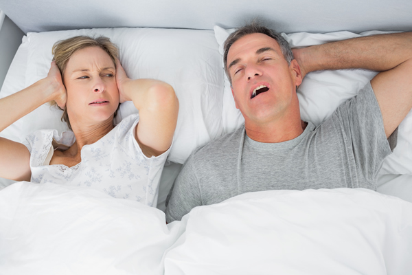 Woman in bed holding her ears shut while partner snores