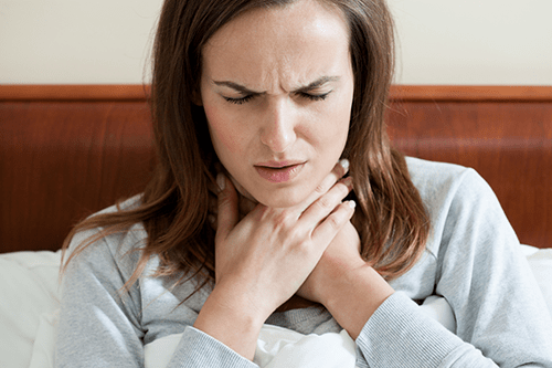 Woman suffering with laryngitis