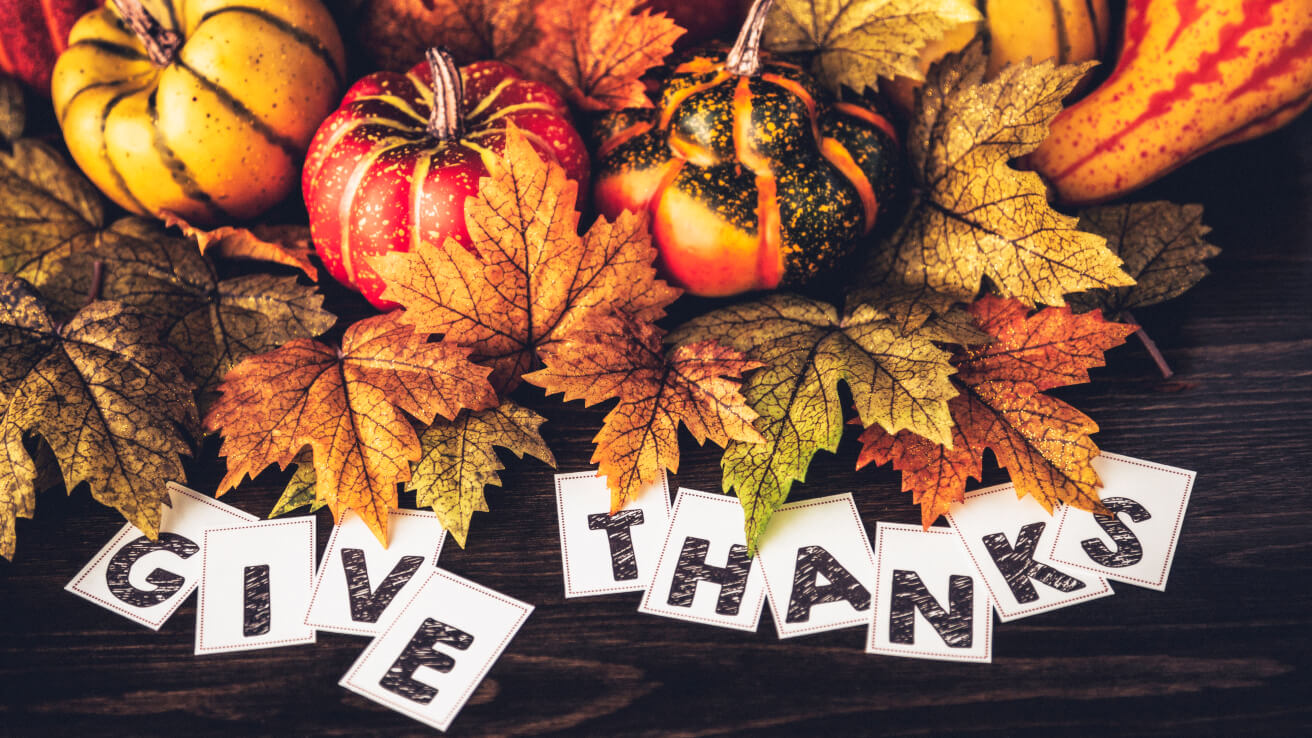 Colorful leaves, pumpkins and gourds with the wording 'Give Thanks' below