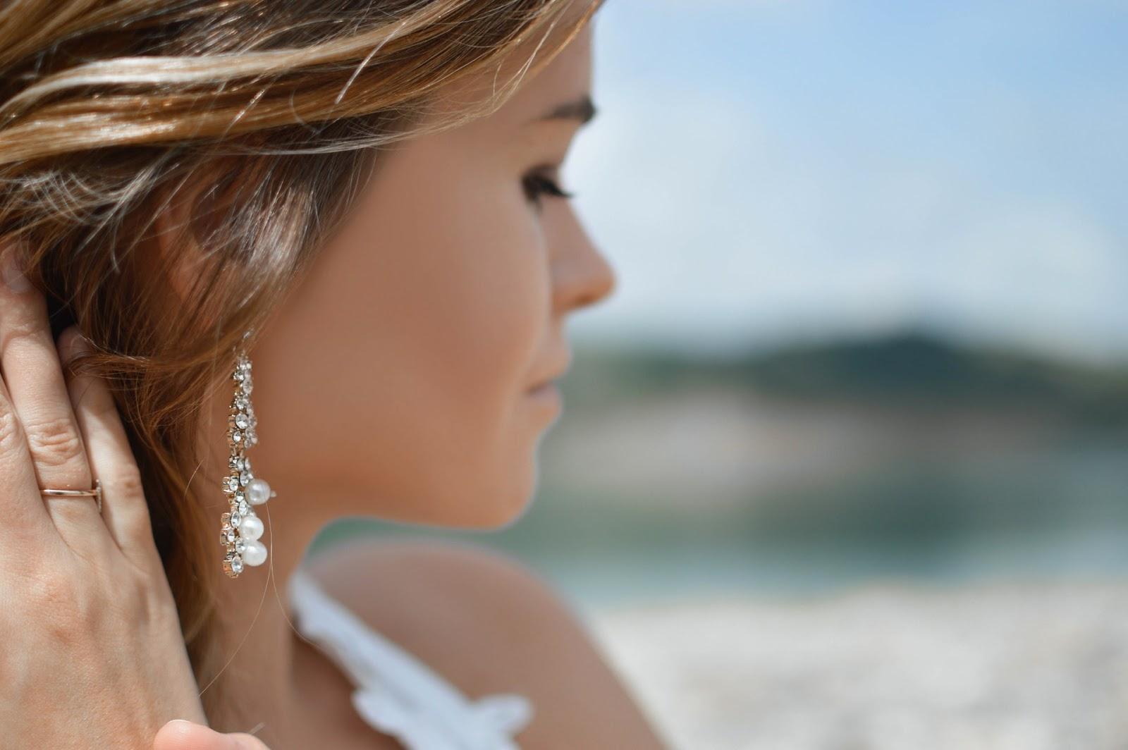 woman wearing single earring with pearls
