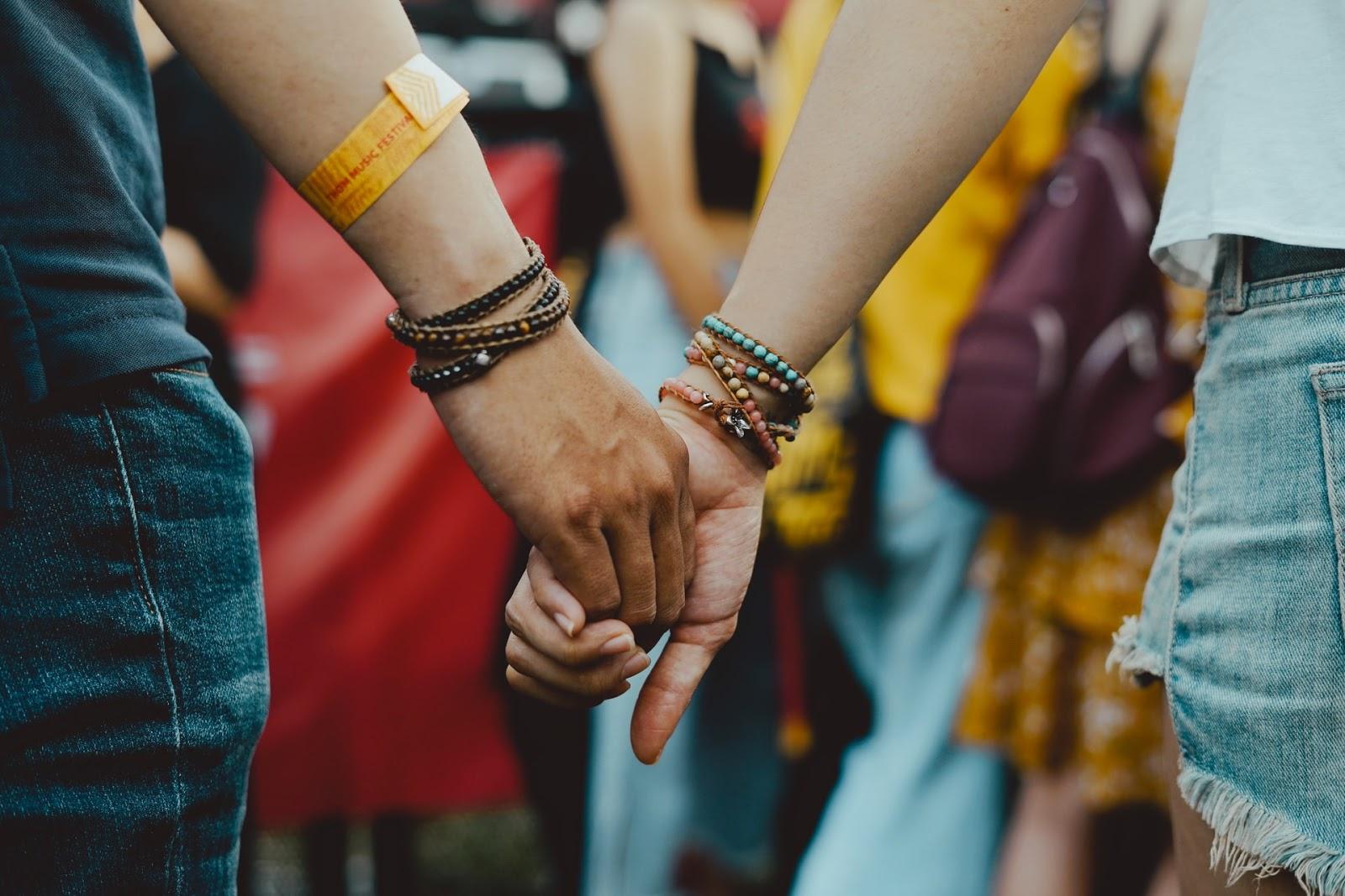 couple wearing bracelets holding hands