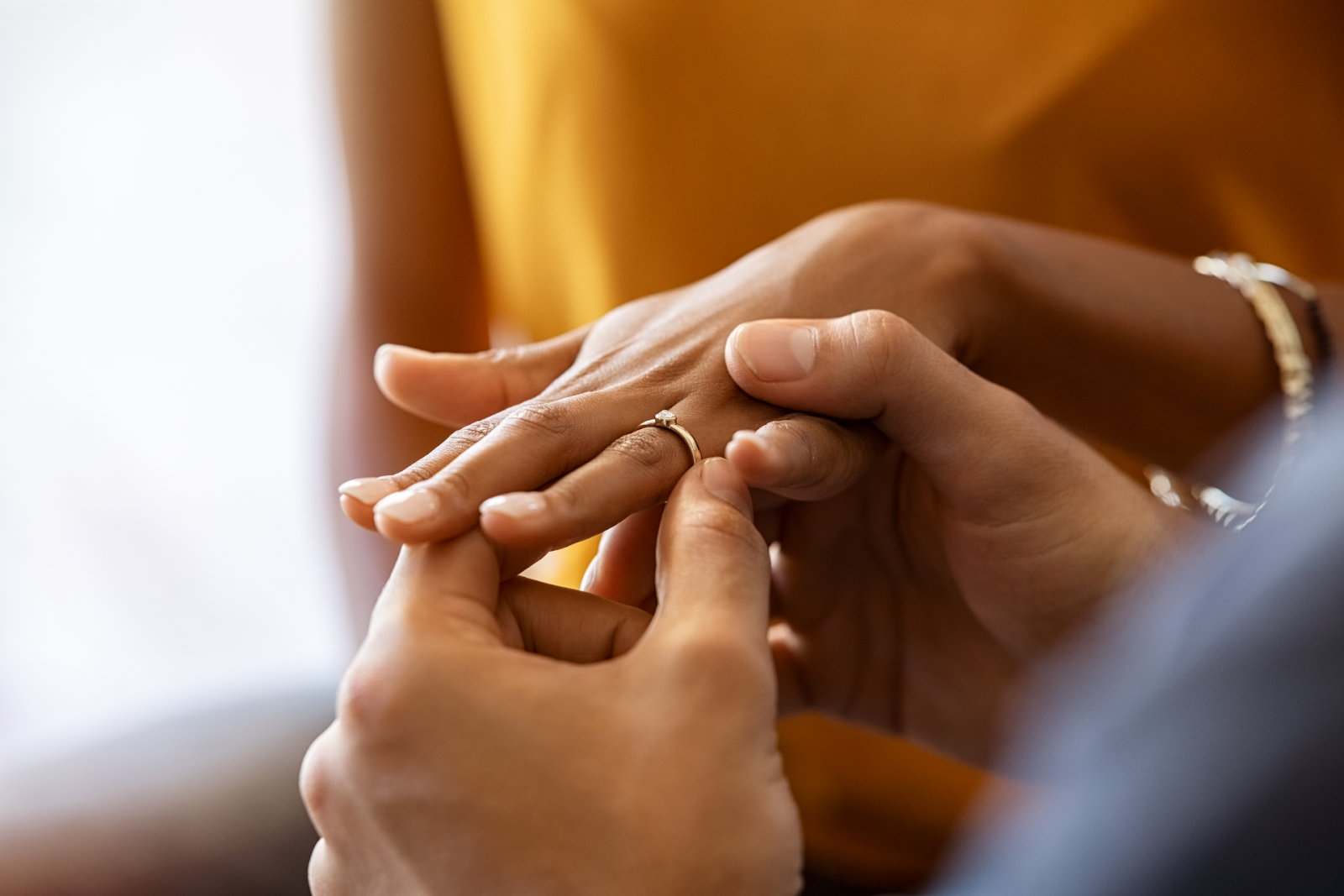 man putting an engagement ring on fiancee's finger