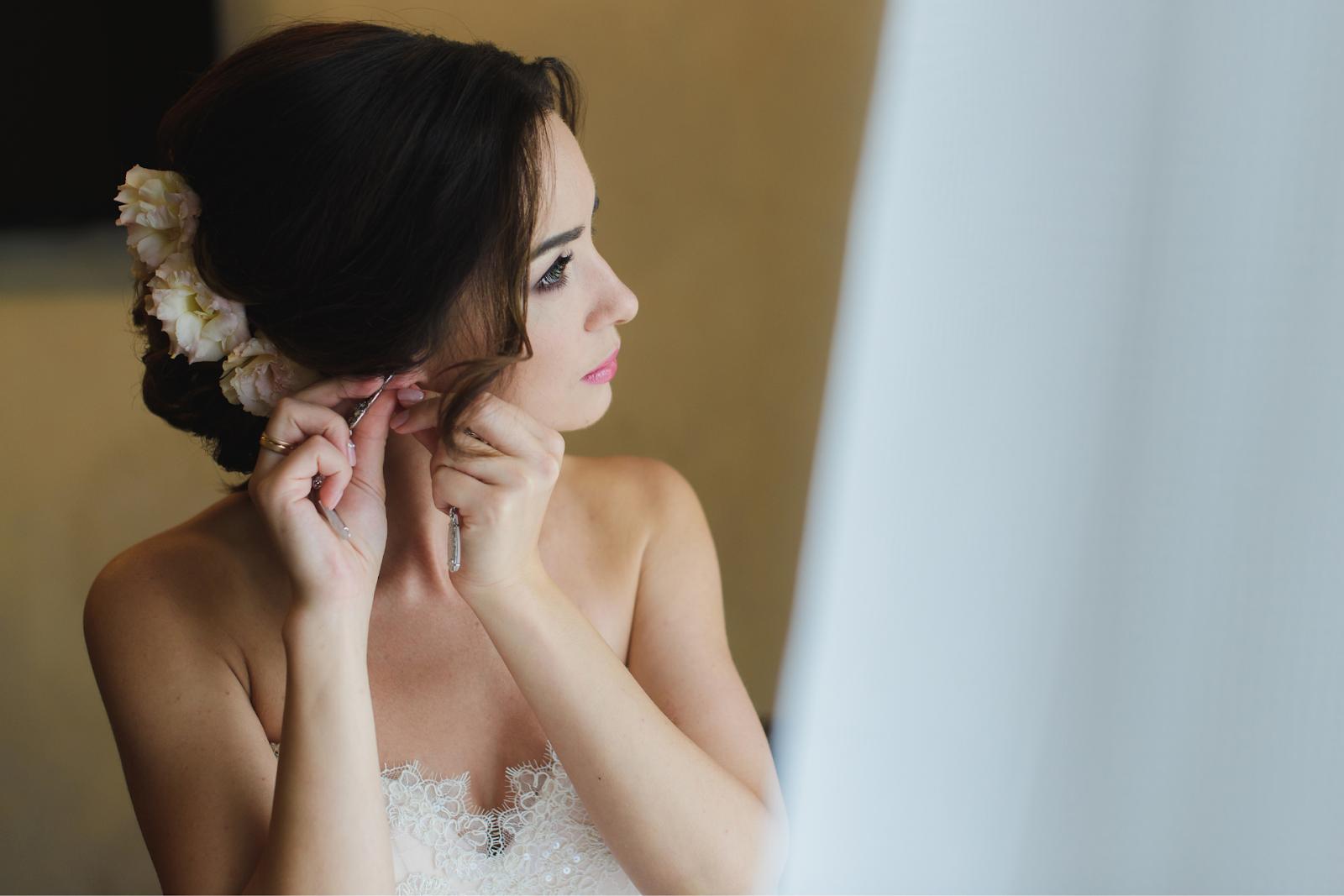 Bride in white wedding dress puts on earring