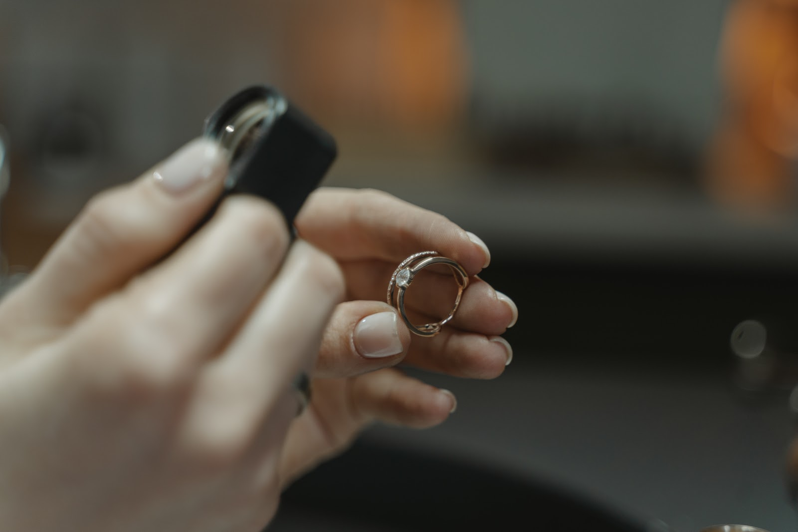 person holding a ring and magnifying glass to observe the ring