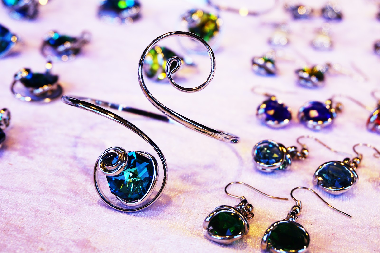 multiple different types of earrings surrounding one large ring with a blue stone